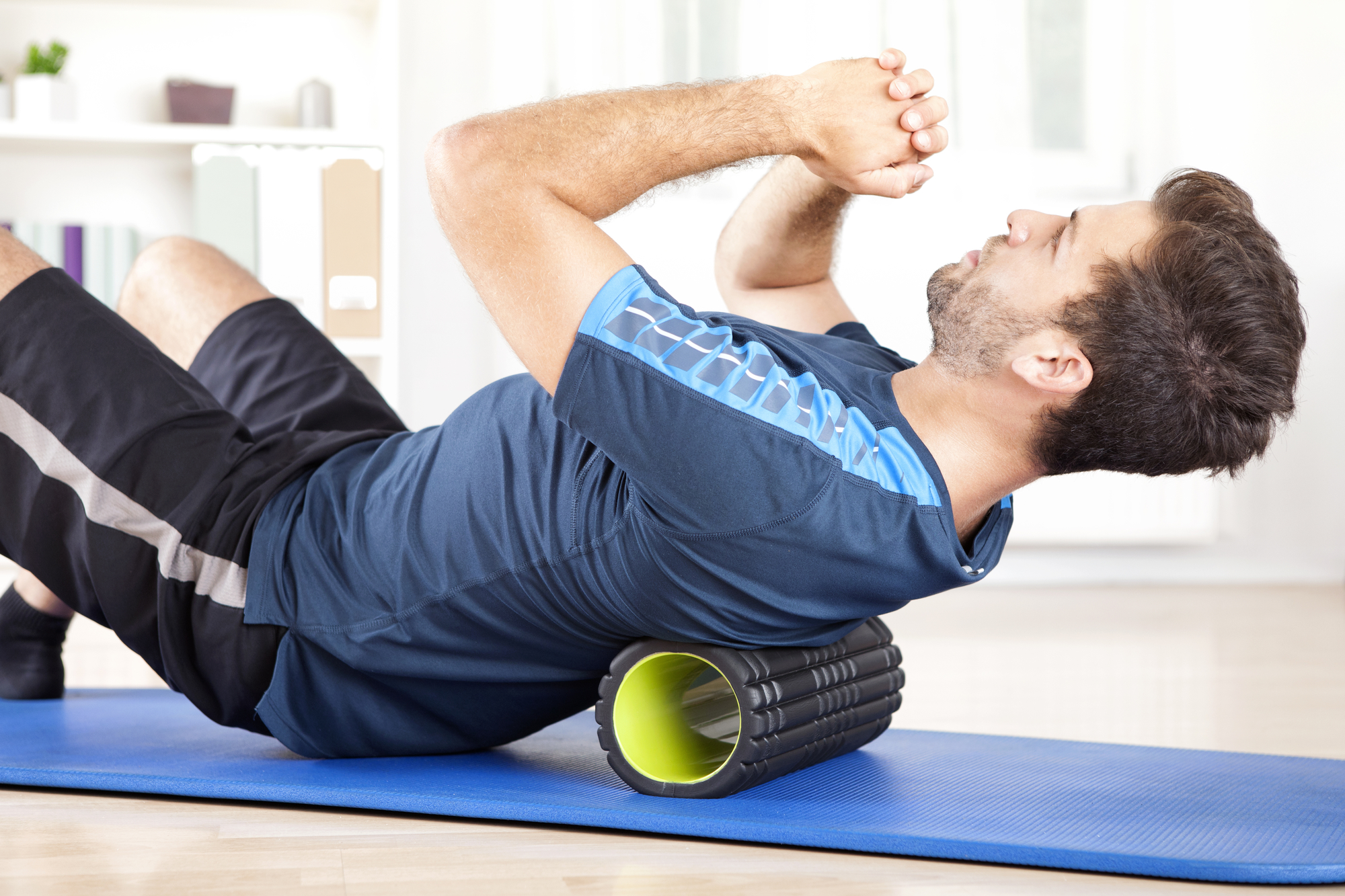 Man Lying on a Foam Roller While Doing an Exercise